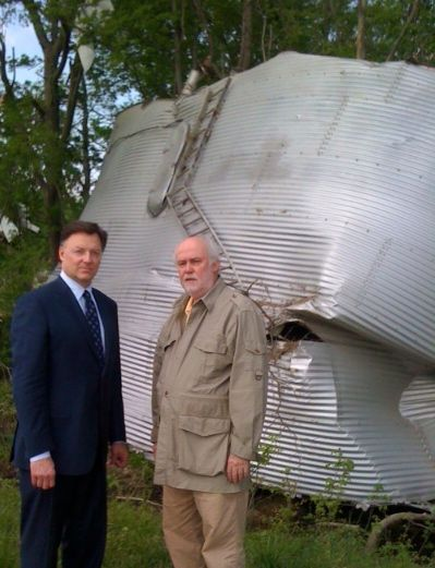 ISBA President John G. Locallo (left) views tornado damage with Shawneetown lawyer James Smith, who lives near Harrisburg. The grain bin came from a nearby farm and was embedded in a grove of trees.