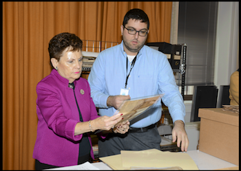 Justice Rita Garman with Archives' conservator Alex Dixon examine a restored oath.