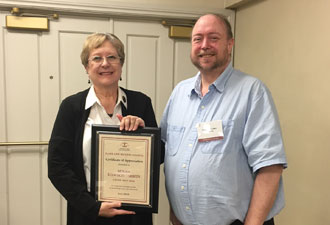 Susan Dawson Tibbits receiving a plaque for her work as chair of elder law from Steve Iden, current chair.