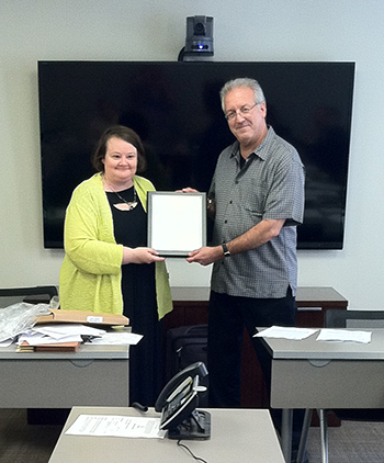 Chair Barbara Goeben presents a plaque to Scott D. Hammer in recognition of his leadership during the inaugural year of the Mental Health Section Council.