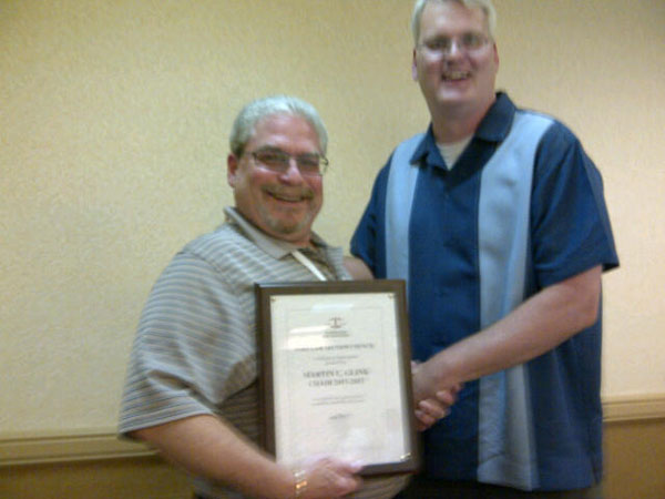 Chair Kevin Veugeler presenting last year's chair Marty Glink with a plaque of appreciation for his efforts