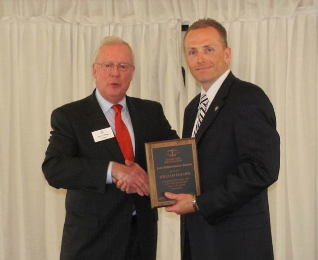 ISBA President John O'Brien presents a Law Enforcement Award to William Holman, Deputy Chief of Police of Glen Ellyn.