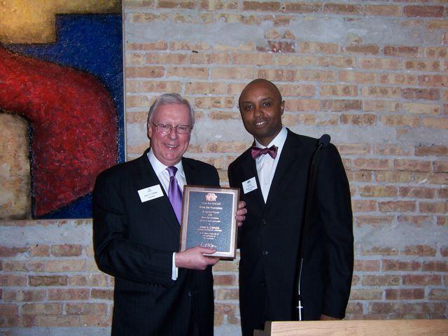 ISBA President John O'Brien receives a commemorative plaque from IBF President Vince Cornelius