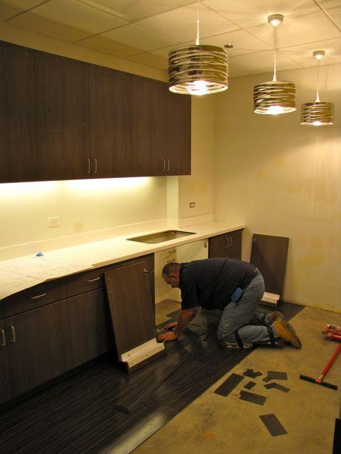 A construction worker installs flooring in the break rooom.