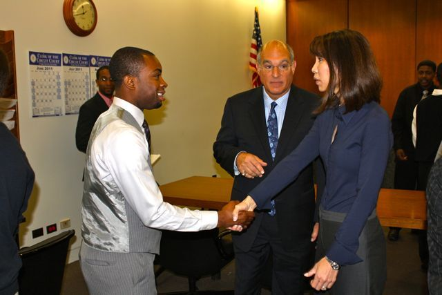 Teacher Tyrese Foreman greets Judge Liu.