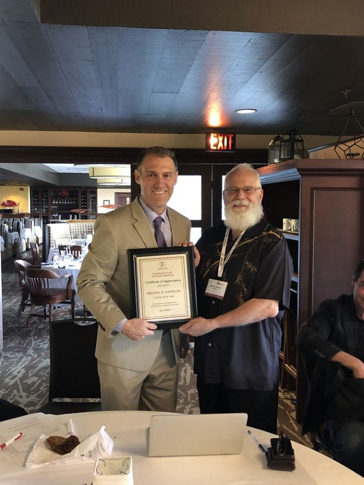 The Insurance Law Section Council's chair Mark Rouleau presents a plaque to ex-officio Michael Hartigan.
