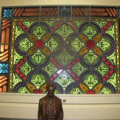 A statue of Abraham Lincoln stands in front of a stained glass window.