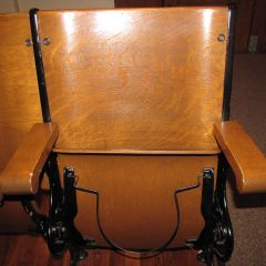 Close-up of seats with antique hat holder underneath