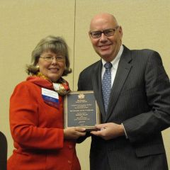 ISBA Board of Governors member Paula Holderman presents the Honorary Fellow Award to Chief Judge James Holderman.