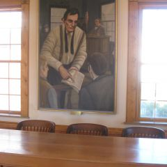 Jury table in Lincoln Courtroom with painting of Lincoln showing Farmers Almanac to jury in background.