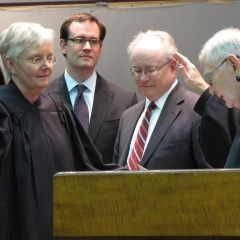Mary Jane Theis (left) is sworn-in by retiring Chief Justice Thomas Fitzgerald as her son and husband look on.