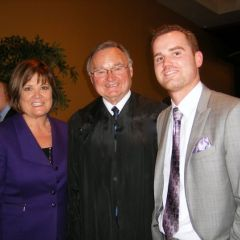 Supreme Court Justice Lloyd Karmeier congratulates new admittee Bryce Joiner and his mother Barbara.